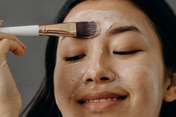 girl applying clay mask to face with brush