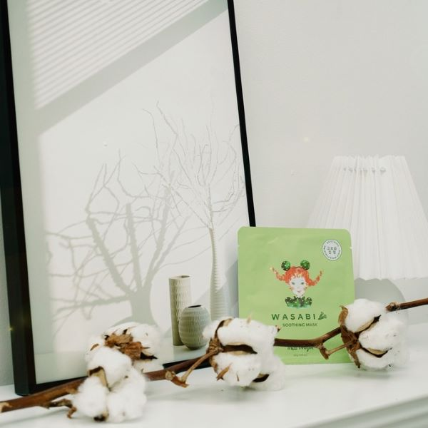 wasabi green korean face mask with cotton plant against white wall