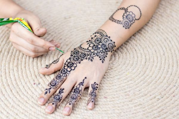 person drawing henna art on back of palm