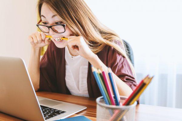 woman biting pencil pen frustrated