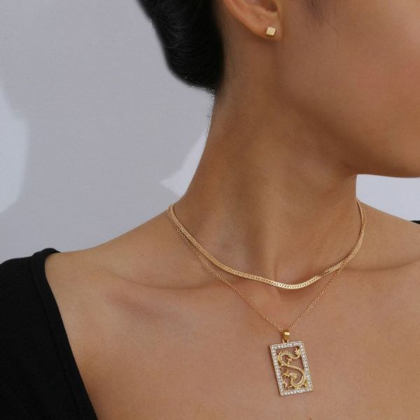 lady wearing gold necklace and ear studs with black top