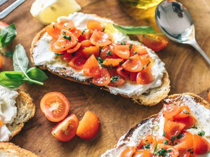 ricotta toast with cherry tomatoes and herbs on wooden board
