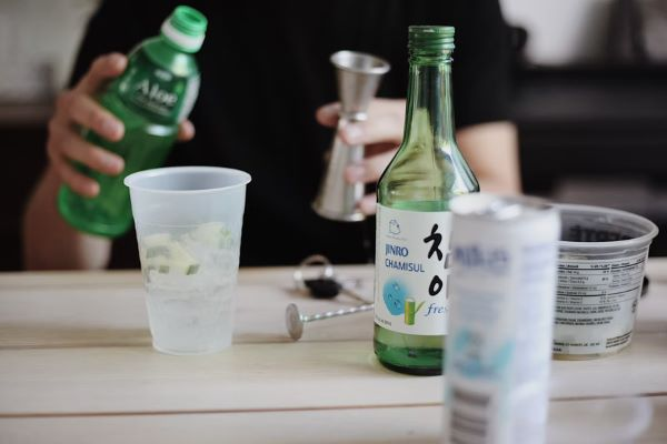 person holding a bottle at a table with soju on top