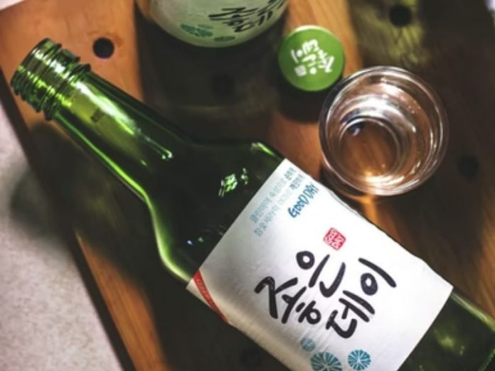 bottle of soju and soju cup on a wooden table