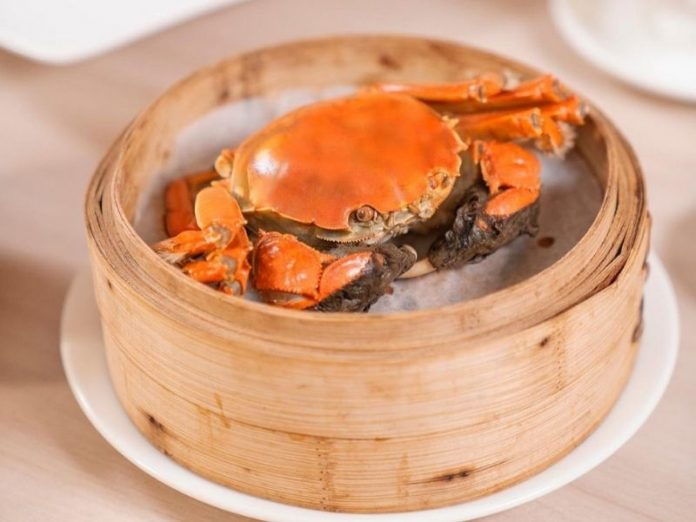Cooked hairy crab in a bamboo steamer on a plate